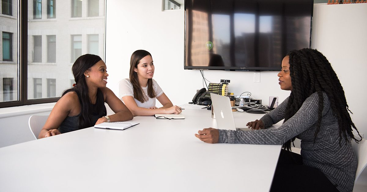Three woman sitting around an office table