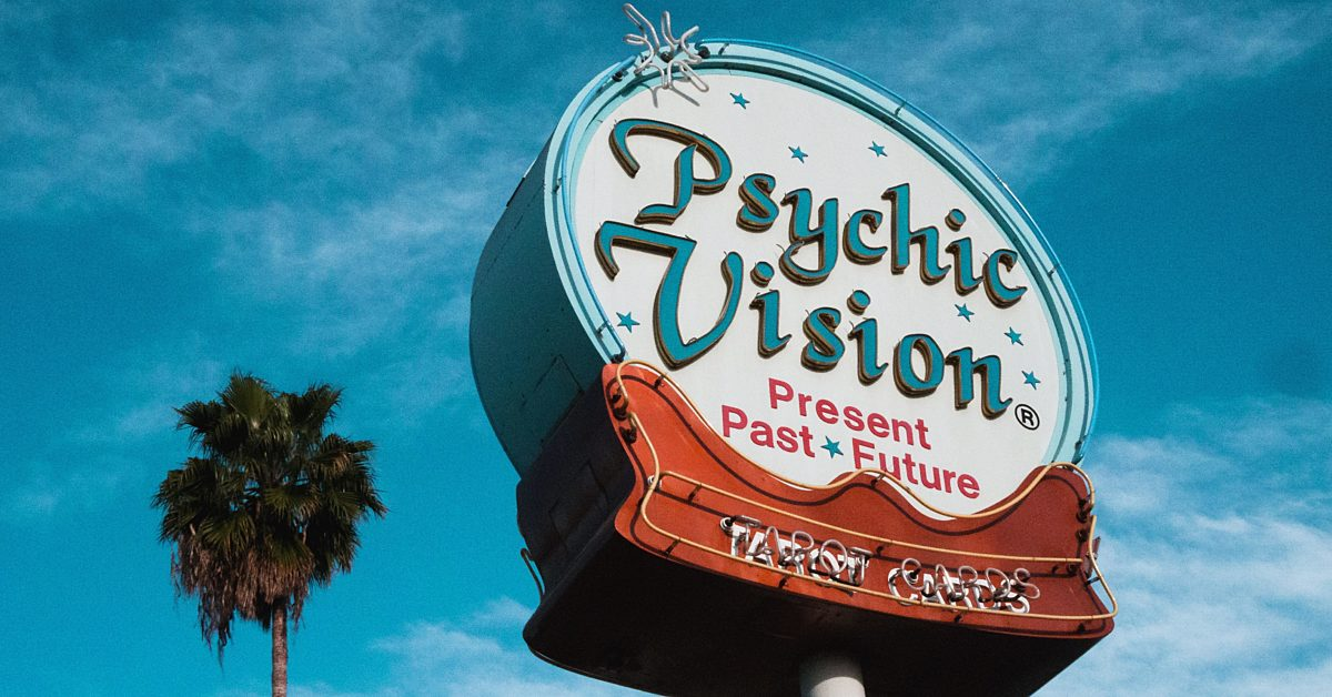"A sign with the words ""Psychic Vision - Present, Past, Future"""
